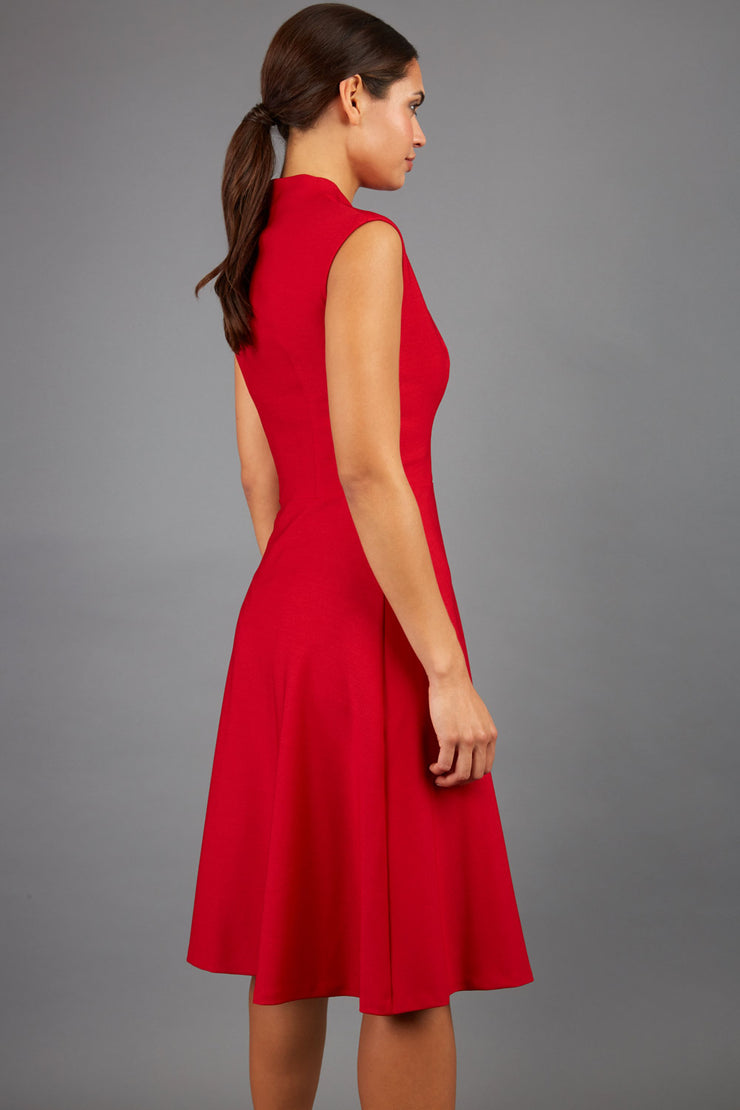 Brunette Model is wearing a sleeveless swing high neck dress in red by Diva Catwalk back image