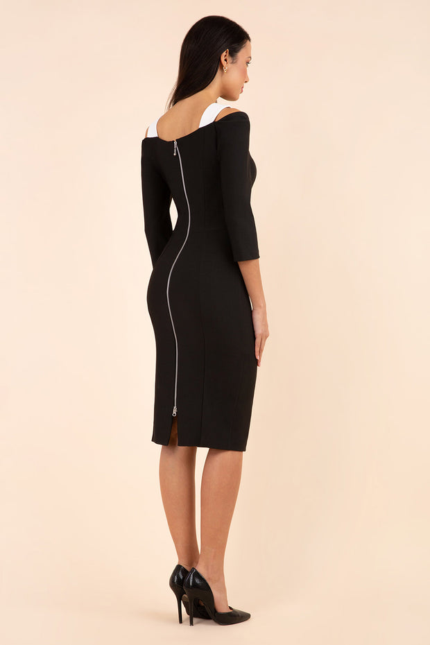 brunette model wearing diva catwalk carolina three quarter sleeve pencil dress with pleating across the tummy and assymetric triangle cuts out on neckline area and cold shoulder in black and white exposed zip from top to bottom back