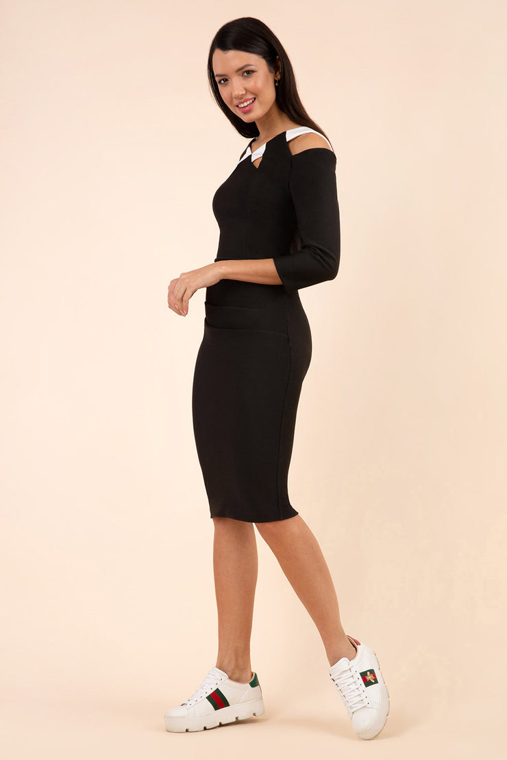 brunette model wearing diva catwalk carolina three quarter sleeve pencil dress with pleating across the tummy and assymetric triangle cuts out on neckline area and cold shoulder in black and white front