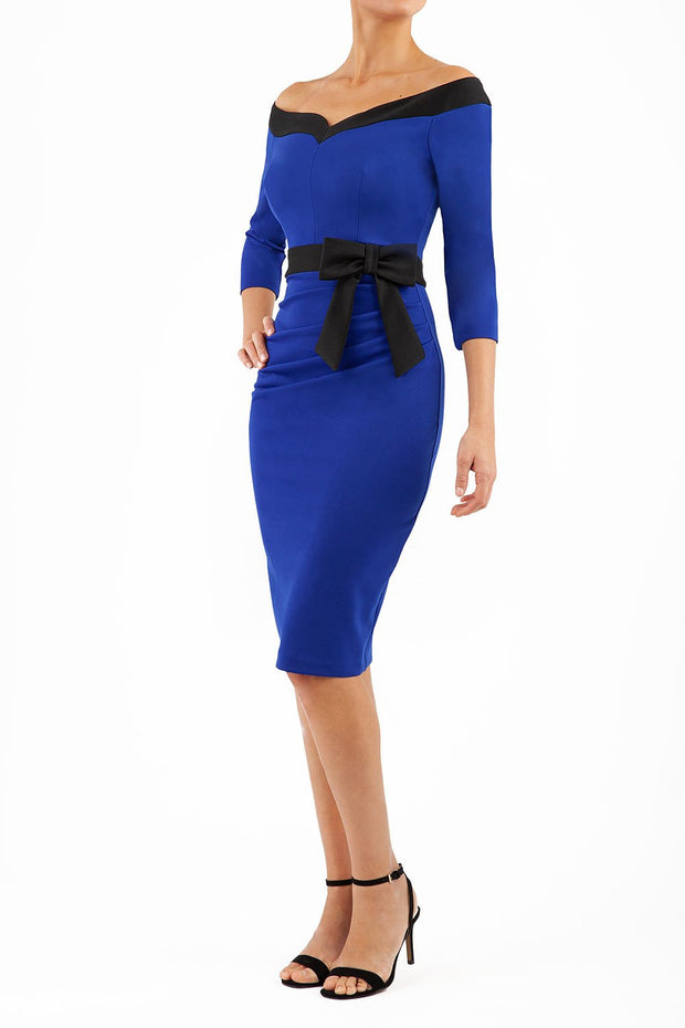blonde model wearing diva catwalk luma pencil skirt dress with contrasting bow off shoulder with sleeves in cobalt blue front