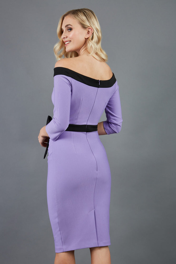 blonde model wearing diva catwalk luma pencil skirt dress with contrasting bow off shoulder with sleeves in lilac wisteria back