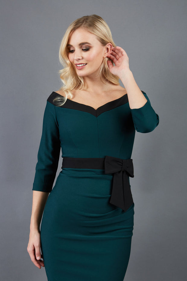 blonde model wearing diva catwalk luma pencil skirt dress with contrasting bow off shoulder with sleeves in forest green front
