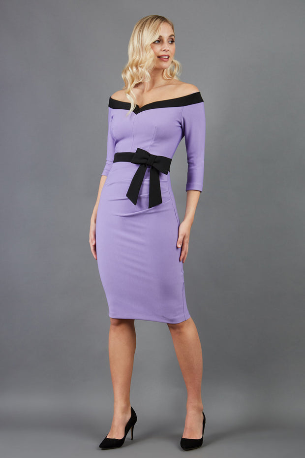 blonde model wearing diva catwalk luma pencil skirt dress with contrasting bow off shoulder with sleeves in lilac wisteria front