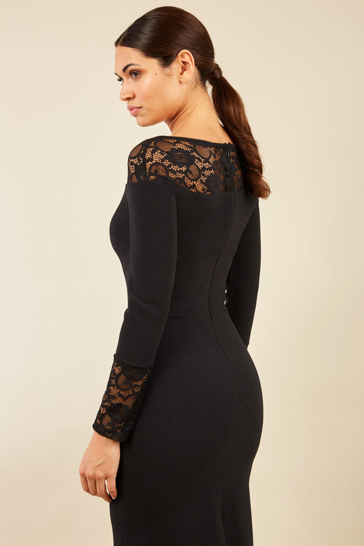 brunette model wearing diva catwalk black lace pencil dress with long sleeves and rounded lace neckline with the lace covering shoulders back