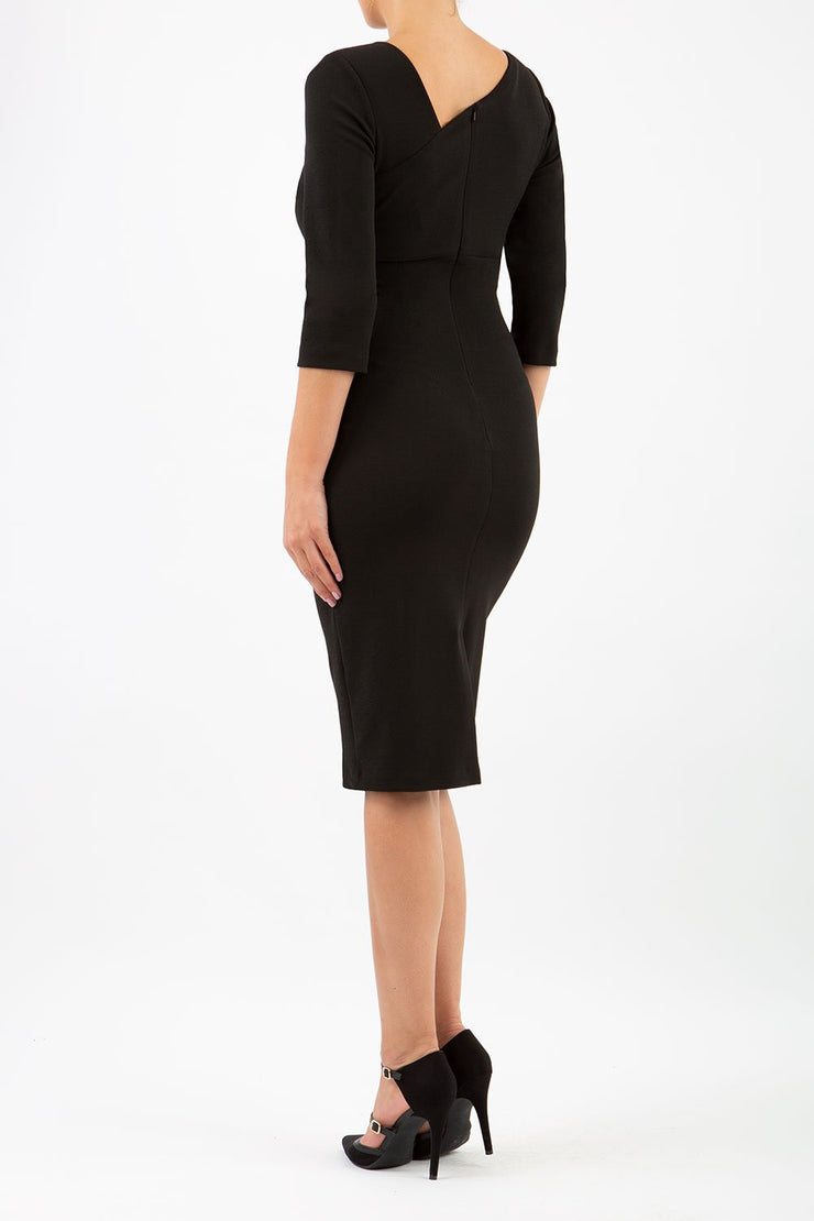 brinette model wearing diva catwalk kubrick pencil-skirt dress with sleeves and asymmetric neckline in black back