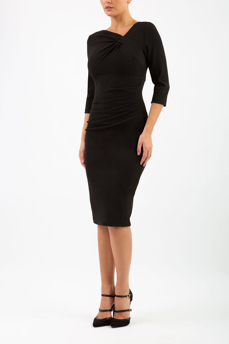 brinette model wearing diva catwalk kubrick pencil-skirt dress with sleeves and asymmetric neckline in black front