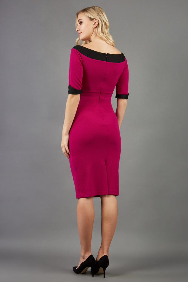 blonde model is wearing diva catwalk fellini sweetheart neckline fitted pencil dress with sleeves with cuff in colour pink with black contrasting detail back