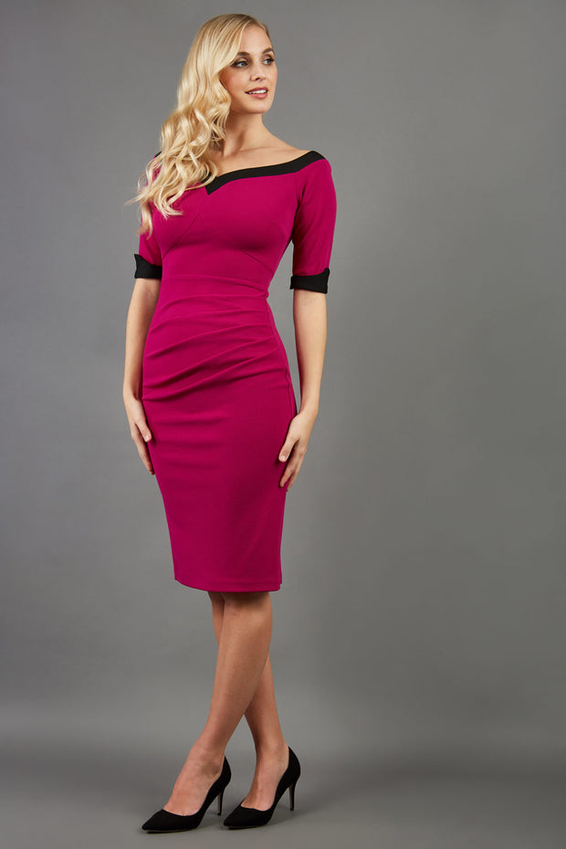 blonde model is wearing diva catwalk fellini sweetheart neckline fitted pencil dress with sleeves with cuff in colour pink with black contrasting detail front