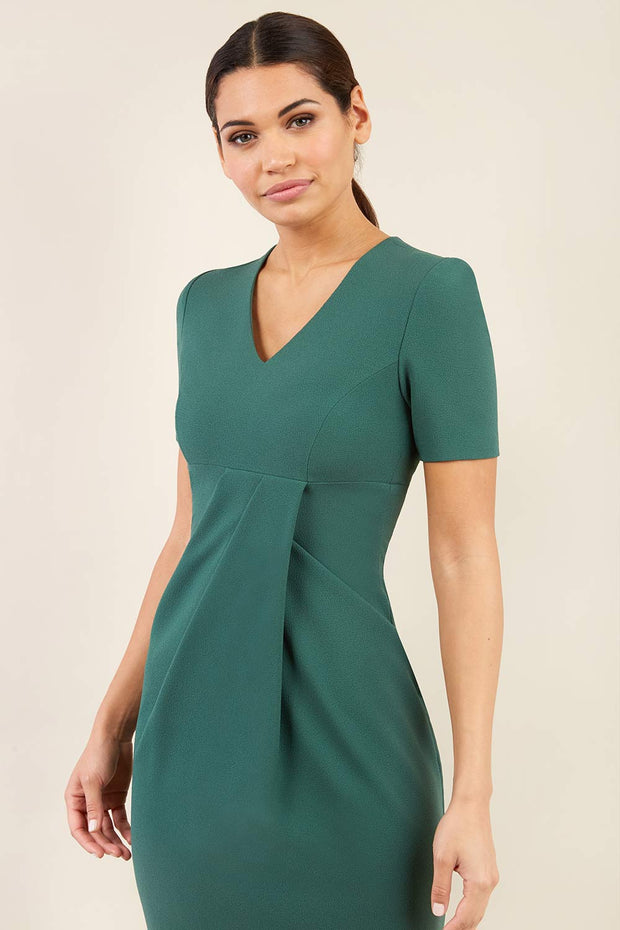 brunette model wearing diva catwalk tregony a-line dress with lowered v-neckline in hunter green and short sleeves front
