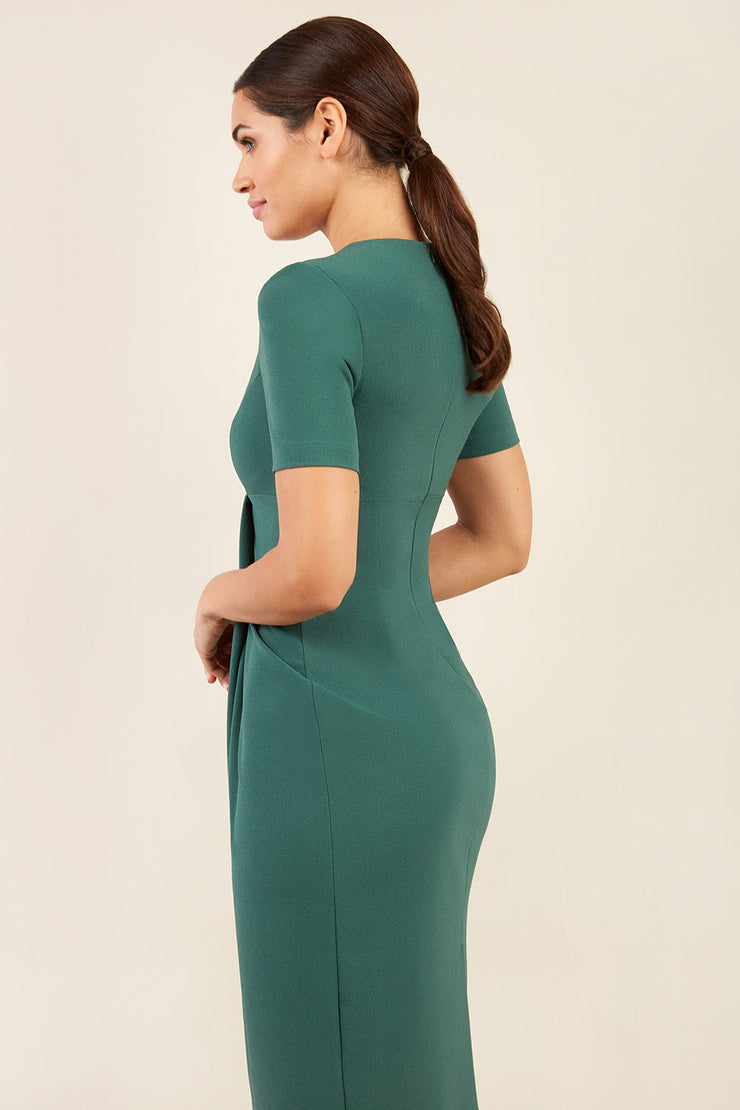 brunette model wearing diva catwalk tregony a-line dress with lowered v-neckline in hunter green and short sleeves back