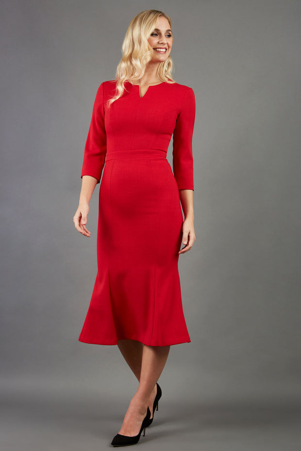 blonde model is wearing diva catwalk senne midaxi sleeved dress with fishtail and rounded neckline with a slit in the middle in red front