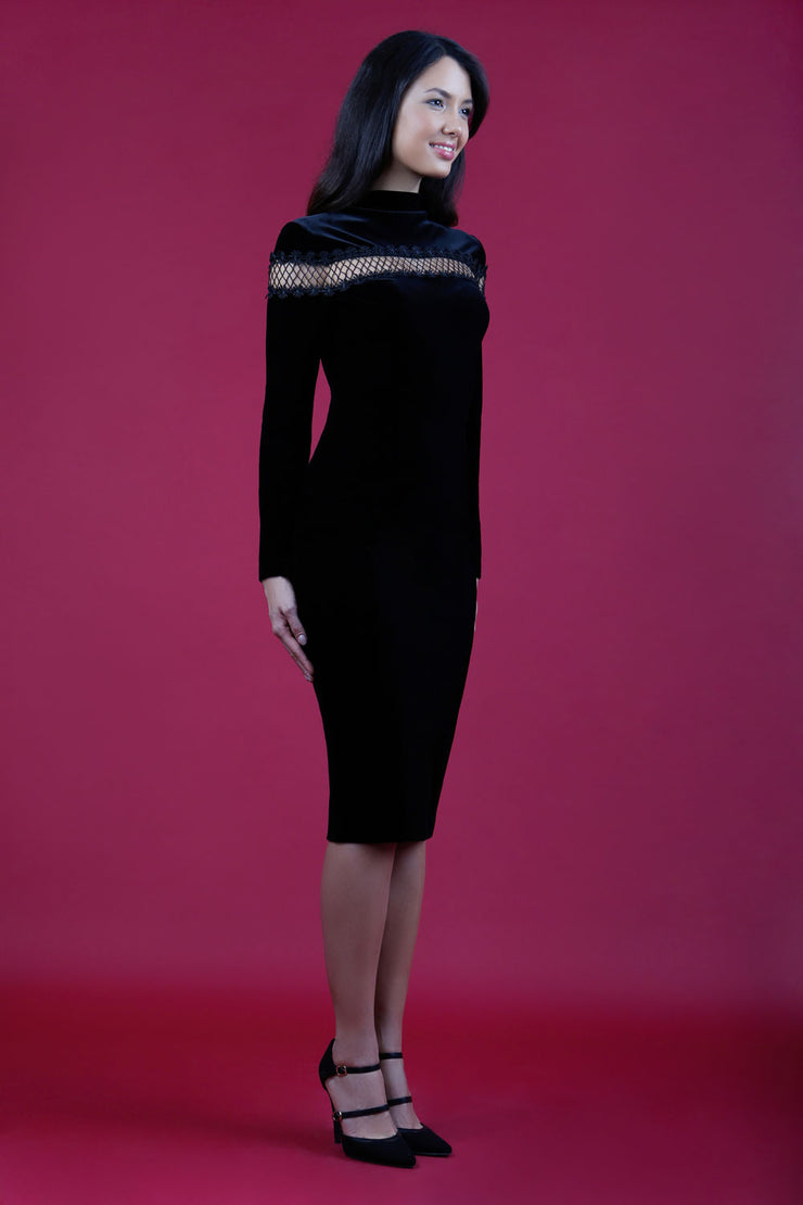 blonde model wearing diva catwalk black pencil dress called trocadero pencil midaxi style with funnel neckline and lace detail and long sleeves front