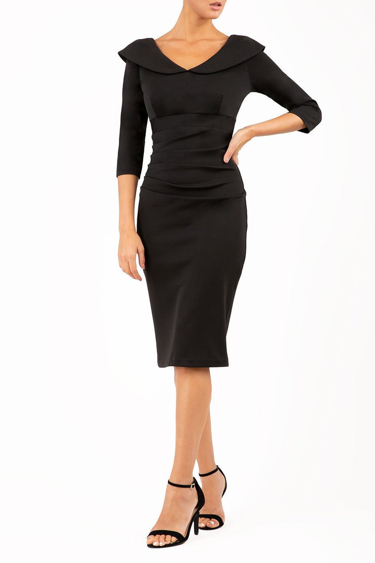 model wearing diva catwalk black pencil-skirt dress  with 3 4 sleeves and pleated pencil skirt and oversized collar front