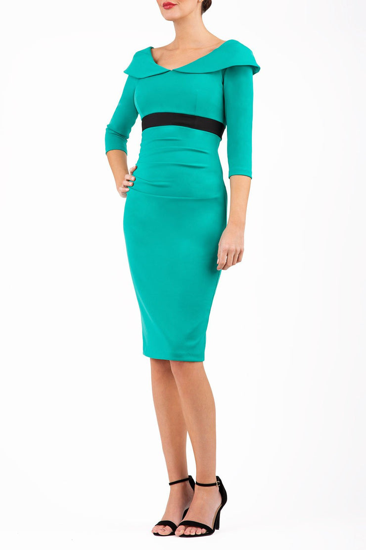 model wearing diva catwalk emerald green pencil-skirt dress  with 3 4 sleeves and pleated pencil skirt and oversized collar front