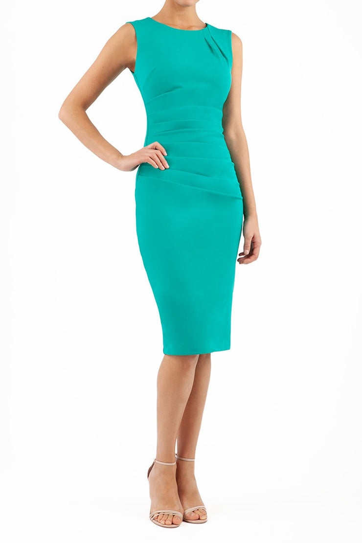 model wearing diva catwalk primula pencil skirt dress in pink with pleating on one side and sleeveless design in colour emerald green front