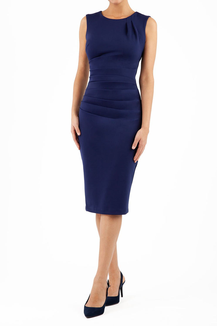 model wearing diva catwalk primula pencil skirt dress in pink with pleating on one side and sleeveless design in colour navy blue front