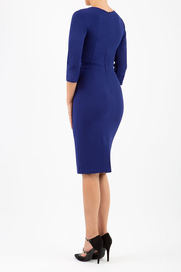 model wearing diva pencil dress tulip design with overlapping pencil skirt with 3 4 sleeves in colour oxford blue back