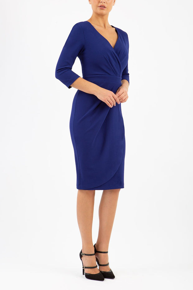 model wearing diva pencil dress tulip design with overlapping pencil skirt with 3 4 sleeves in colour oxford blue front