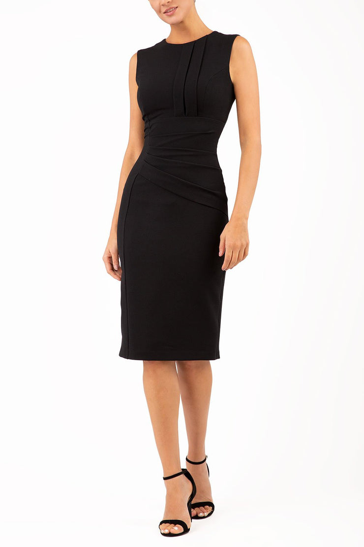 Model wearing the Diva Clara Pencil dress with vertical pleat detailing at bust sleeveless design in black front image