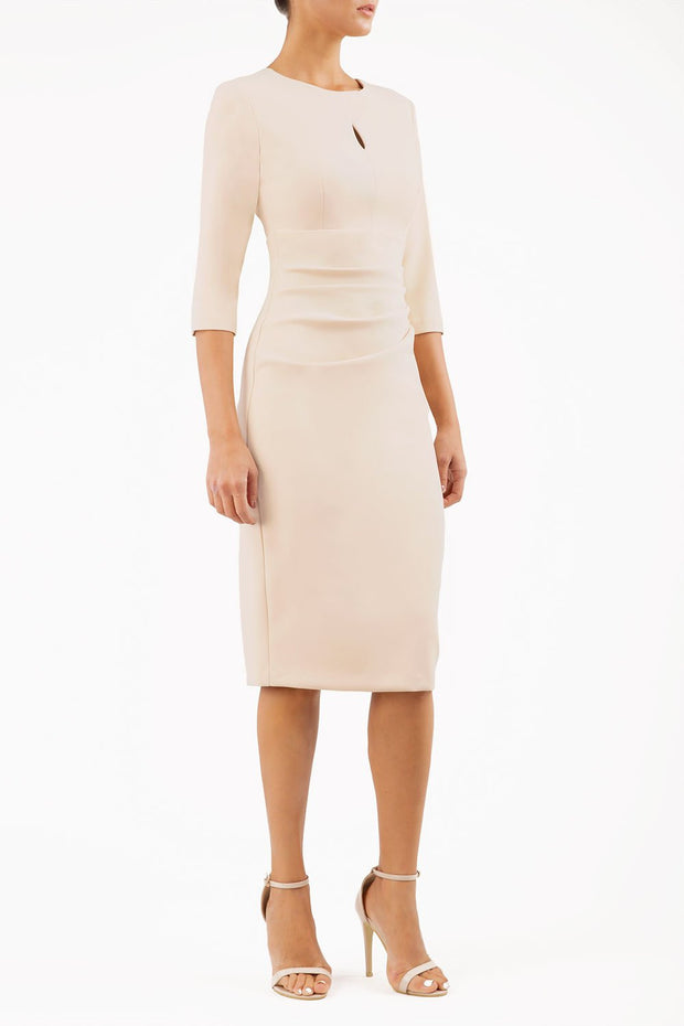 brunette model wearing diva catwalk ubrique pencil dress with a keyhole detail and sleeves in sandshell beige front