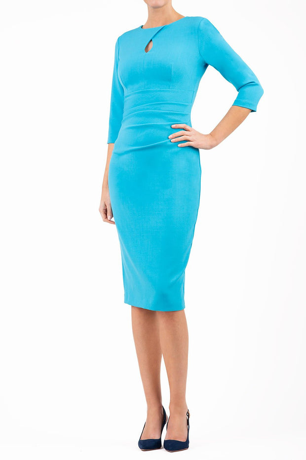 brunette model wearing diva catwalk ubrique pencil dress with a keyhole detail and sleeves in azure blue front