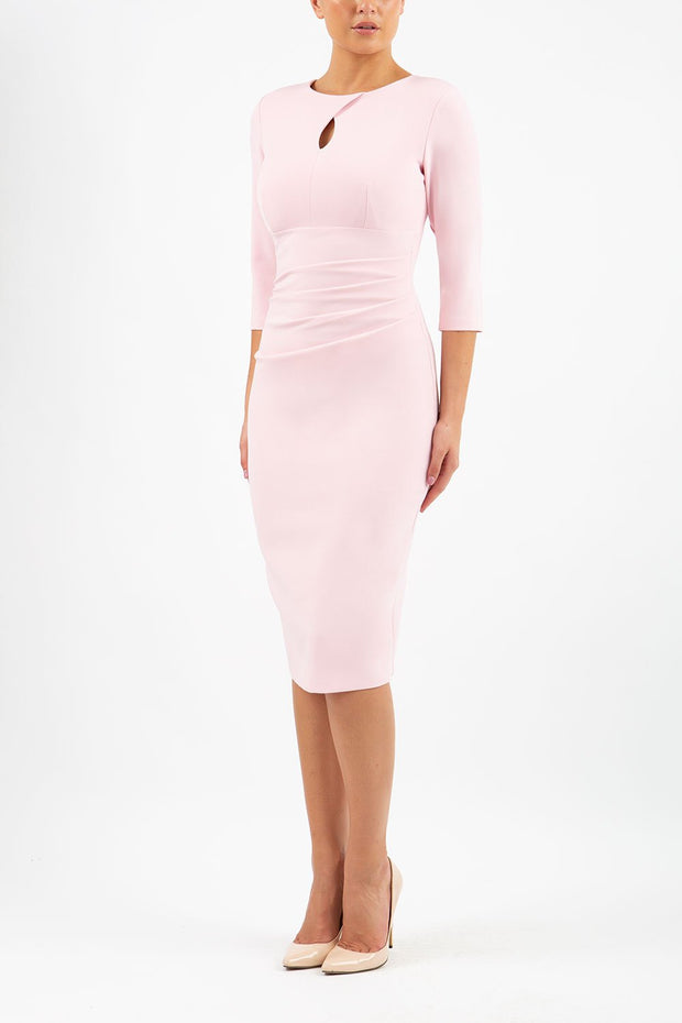 brunette model wearing diva catwalk ubrique pencil dress with a keyhole detail and sleeves in crystal pink front