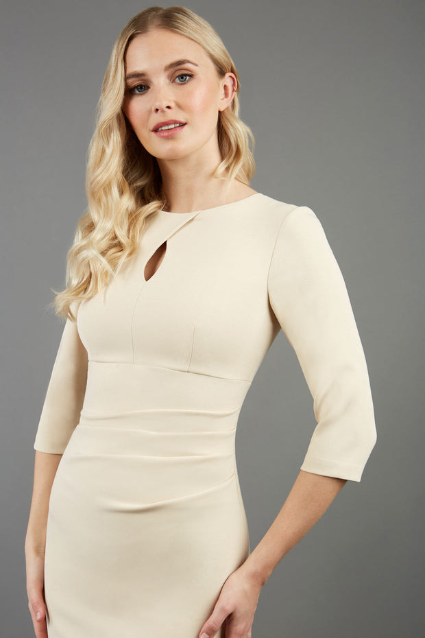 blonde model wearing diva catwalk ubrique pencil dress with a keyhole detail and sleeves in sandshell beige front