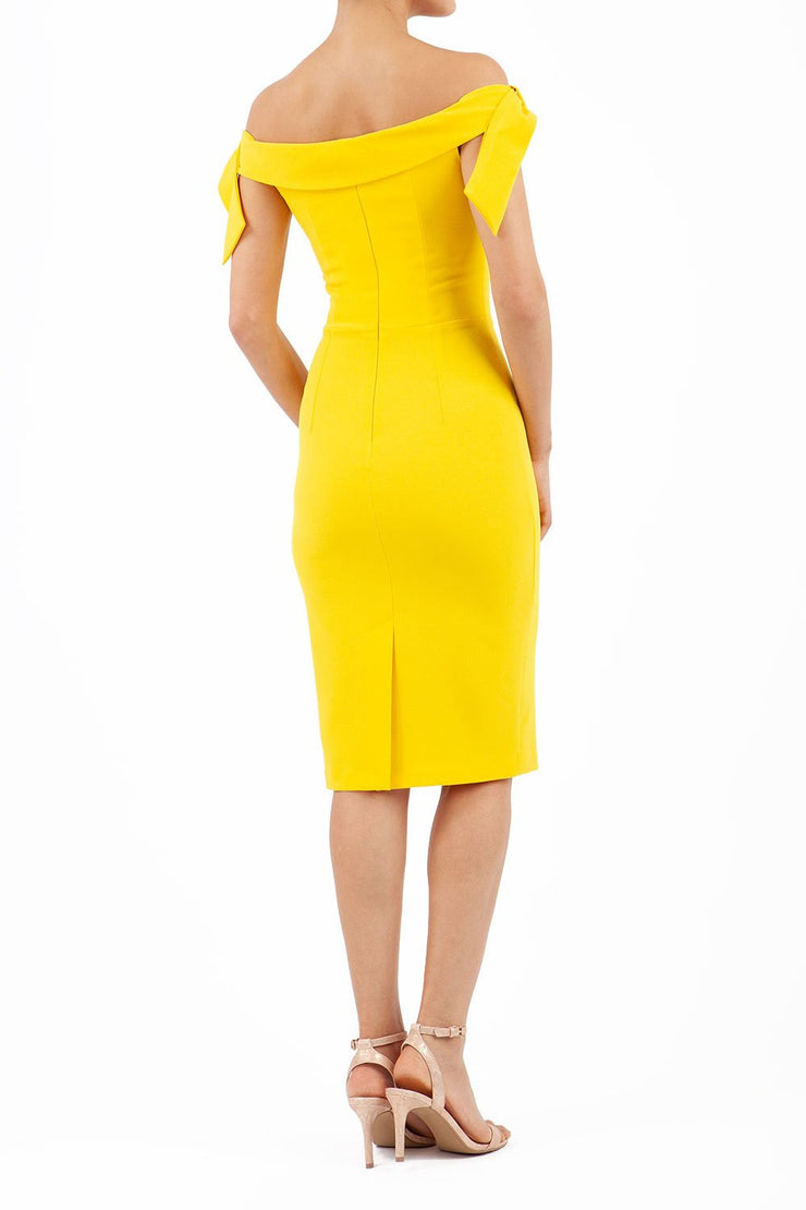 Model wearing the Diva Calista dress, off shoulder design, sleeveless pencil in freesia yellow back image