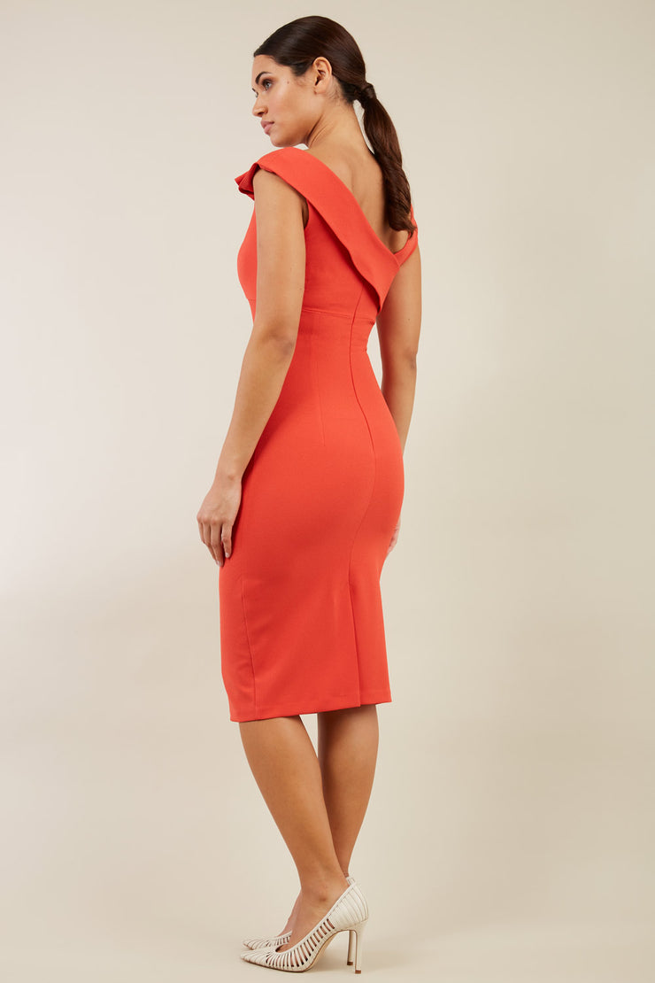 brunette model wearing diva catwalk rosita pencil skirt fitted dress with asymmetric neckline and bow detail at the top and it is a sleeveless design  with empire waistline in orange back