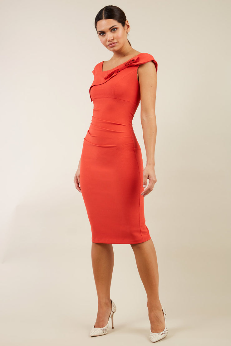 brunette model wearing diva catwalk rosita pencil skirt fitted dress with asymmetric neckline and bow detail at the top and it is a sleeveless design  with empire waistline in orange front