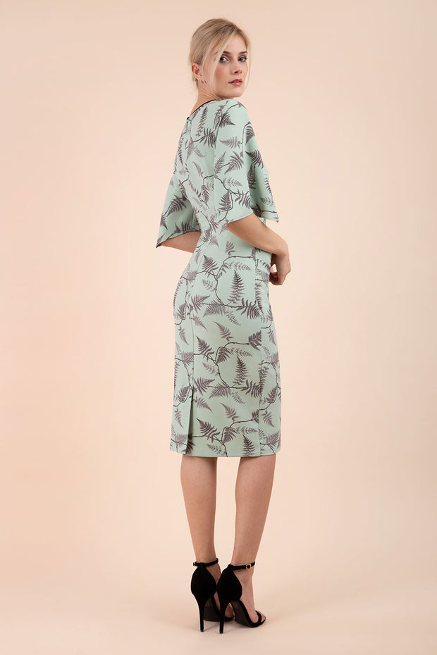 Model wearing the Diva Memphis Print dress dress in pencil dress design in deco green fern print front image