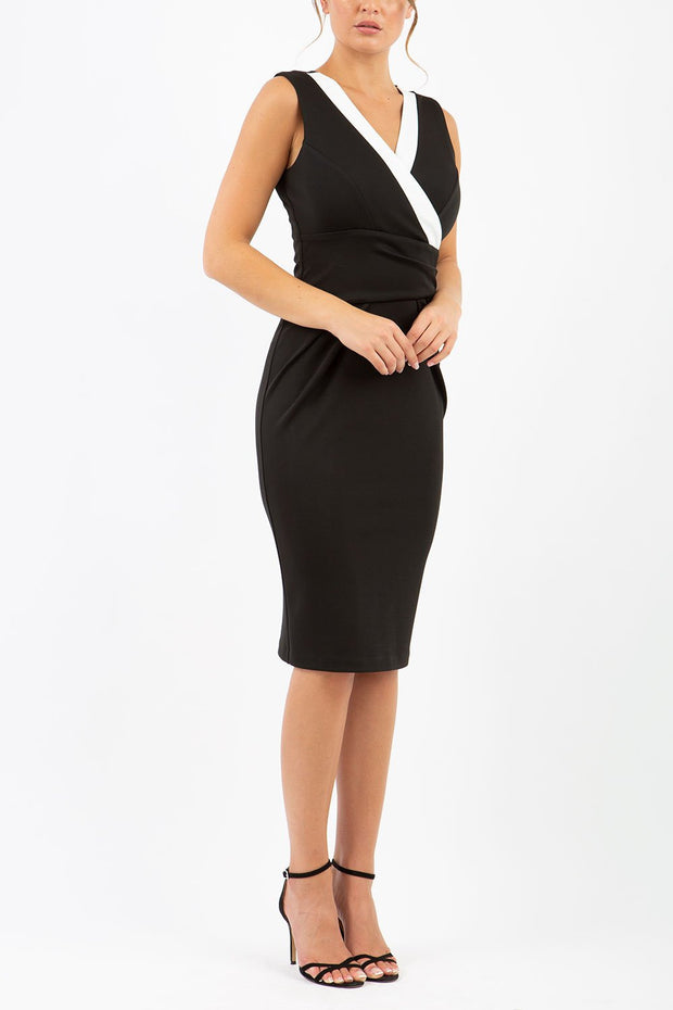 model wearing diva catwalk triton pencil sleeveless dress with overlapping front panels and low v-neckline in black and white front