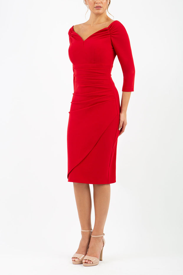 brunette model wearing diva catwalk evening pencil dress off shoulder with sleeves and pleated pencil skirt in colour scarlet red front