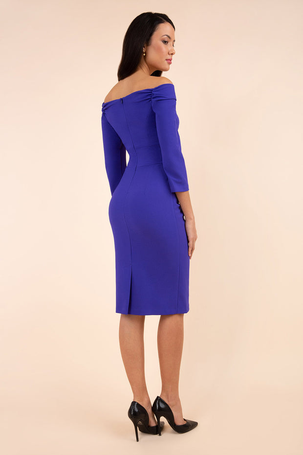 brunette model wearing diva catwalk evening pencil dress off shoulder with sleeves and pleated pencil skirt in colour indigo blue back