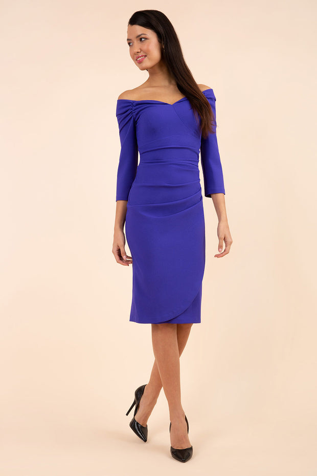 brunette model wearing diva catwalk evening pencil dress off shoulder with sleeves and pleated pencil skirt in colour indigo blue front
