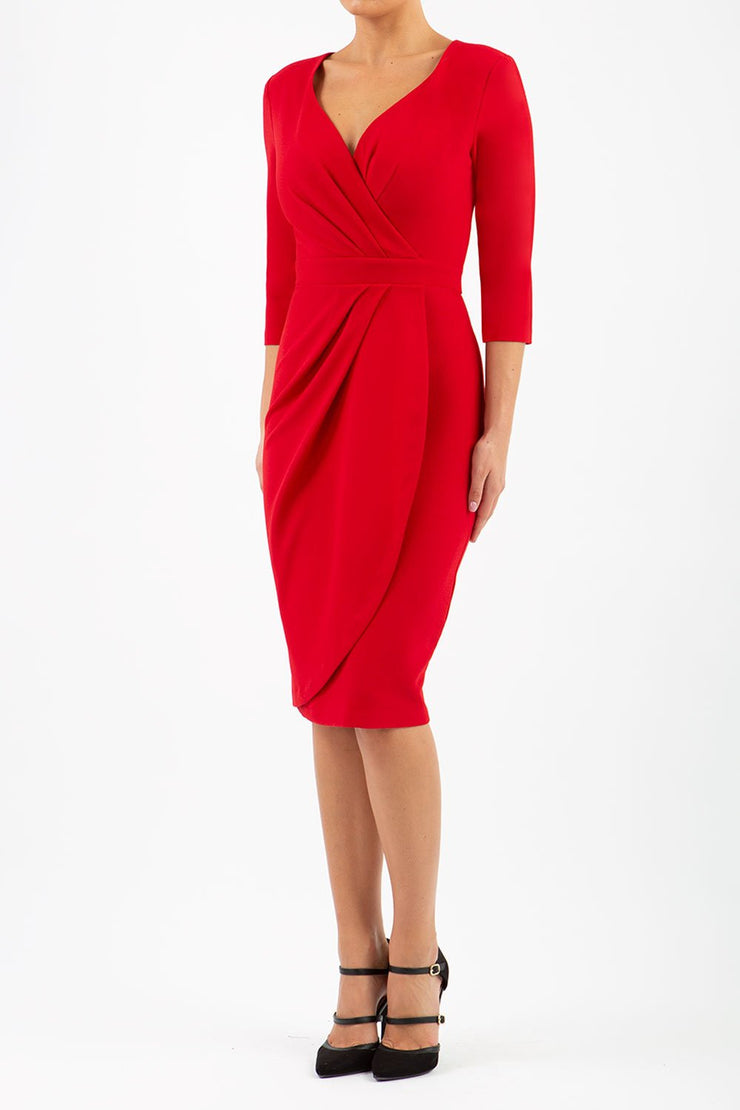 model wearing diva pencil dress tulip design with overlapping pencil skirt with 3 4 sleeves in colour scarlet red front