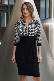 Model wearing the Diva Costwold Tie Print Dress with contrasting top and skirt, slit at neckline and tie detail in dogtooth print front image