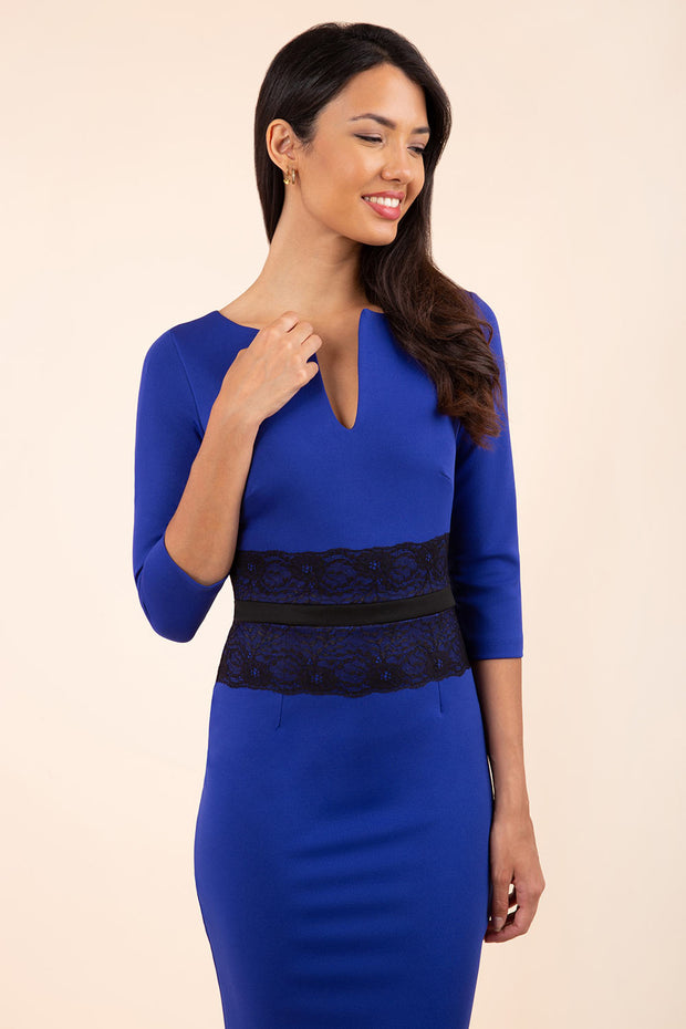 brunette model wearing diva catwalk longleat royal blue pencil dress with sleeves and black lace detail across the tummy front