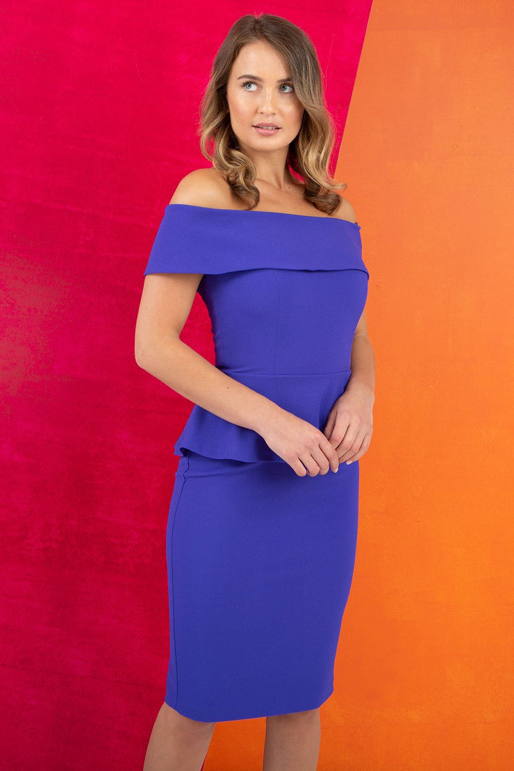 blonde model wearing diva catwalk peplum pencil skirt dress in spectrum indigo colour off shoulder bardot neckline front