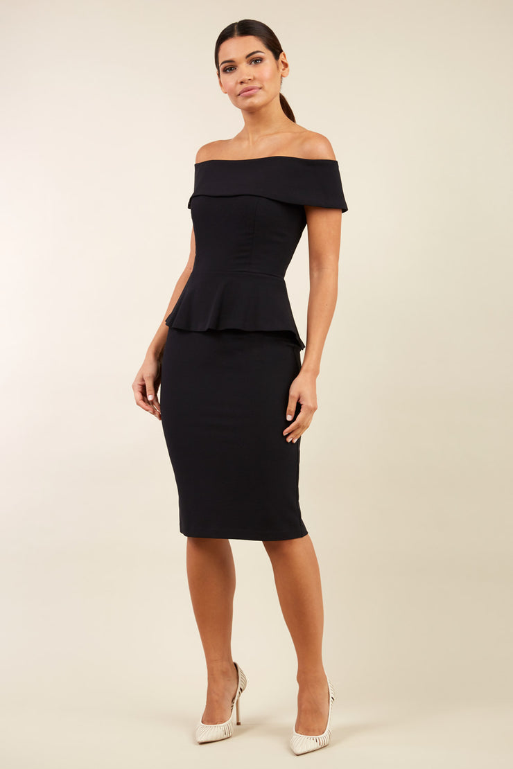 brunette model wearing diva catwalk peplum pencil skirt dress in black colour off shoulder bardot neckline front