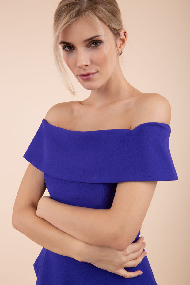 blonde model wearing diva catwalk peplum pencil skirt dress in indigo blue colour off shoulder bardot neckline front