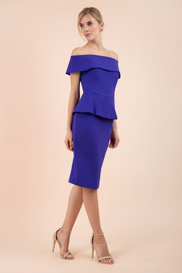 blonde model wearing diva catwalk peplum summer pencil dress in indigo blue colour off shoulder bardot neckline front