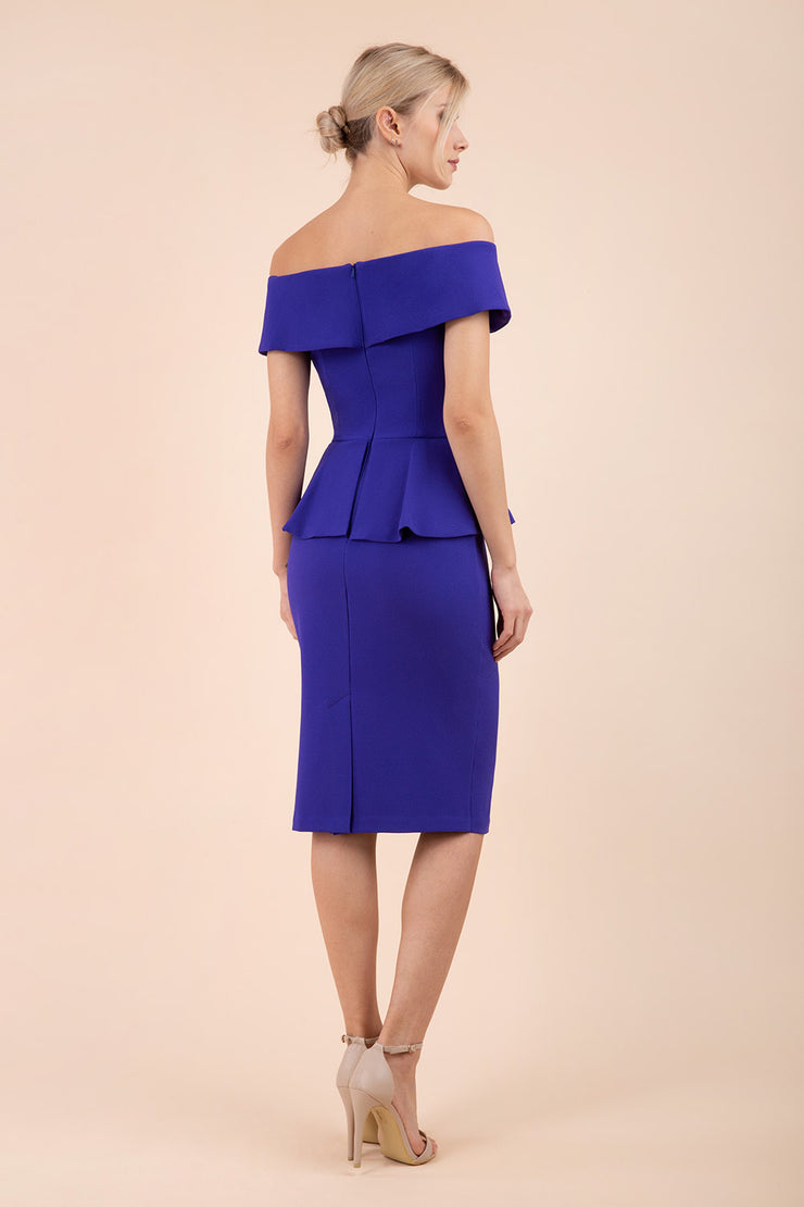 blonde model wearing diva catwalk peplum pencil skirt dress in spectrum indigo colour off shoulder bardot neckline back
