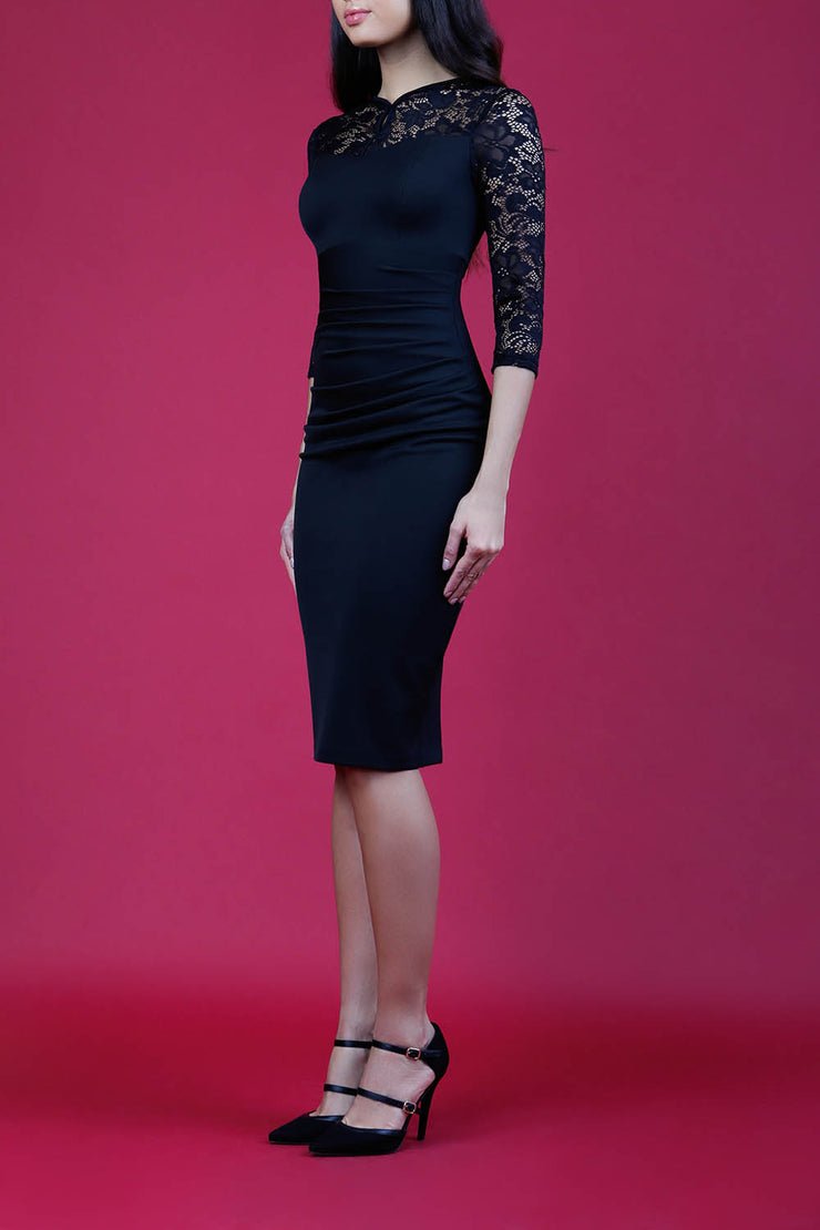 blonde model wearing diva catwalk haversham three quarter contrast pencil dress with lace detail across arms and neckline with pleating cross body in black and black front