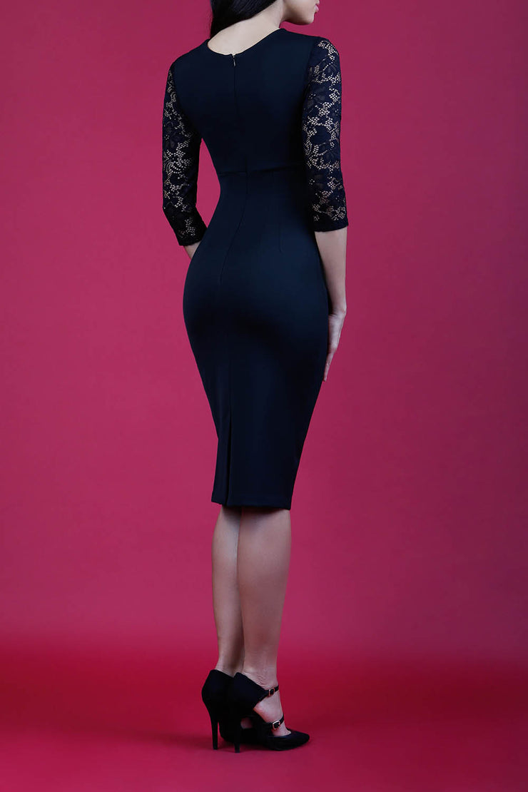 blonde model wearing diva catwalk haversham three quarter contrast pencil dress with lace detail across arms and neckline with pleating cross body in black and black back