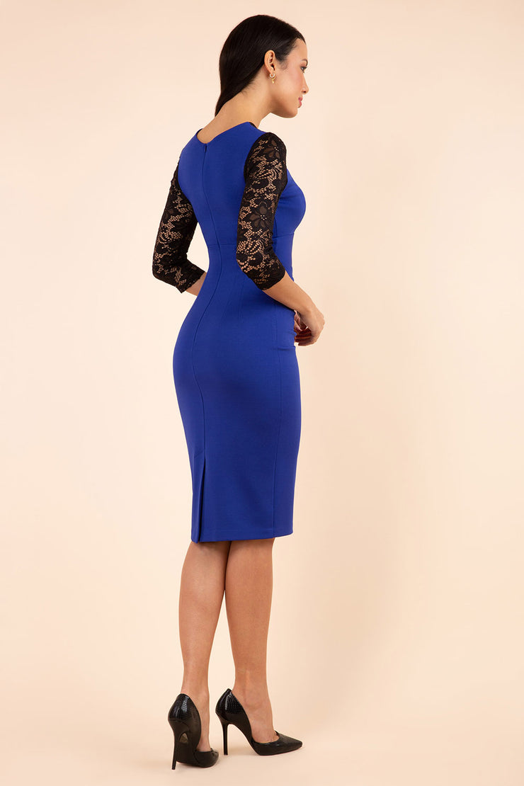 blonde model wearing diva catwalk haversham three quarter contrast pencil dress with lace detail across arms and neckline with pleating cross body in cobalt blue and black back