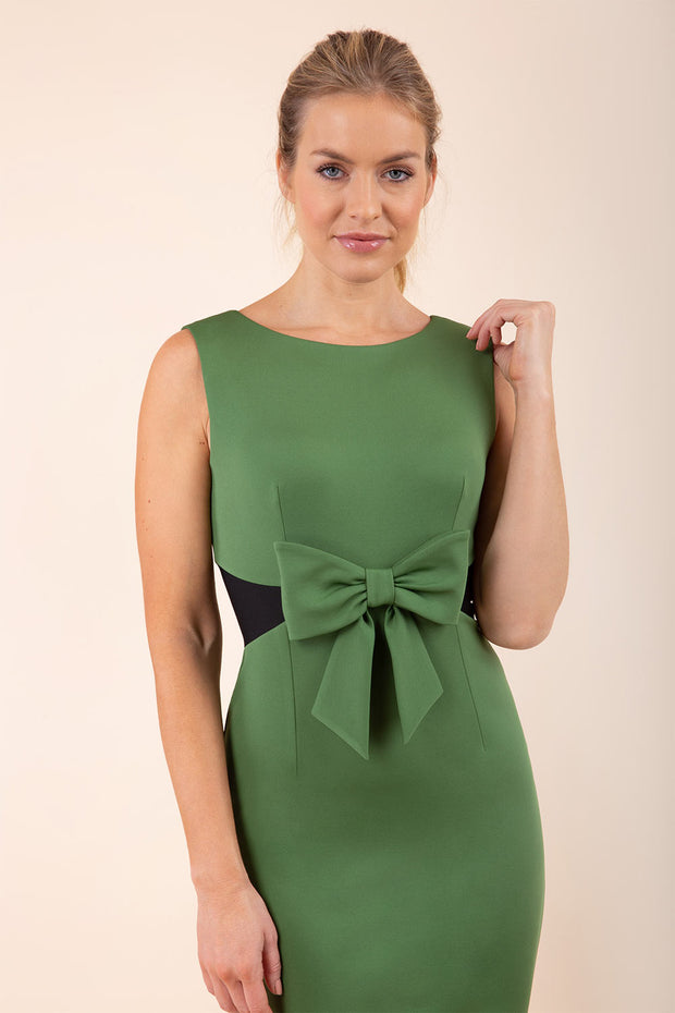 blonde model wearing Diva Catwalk Pencil sleeveless dress with rounded neckline and bow detail at the front with a contrasting black band in vineyard green front