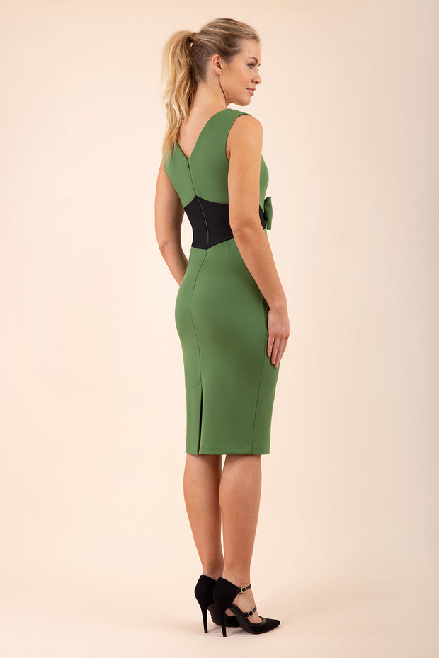 blonde model wearing Diva Catwalk Pencil sleeveless dress with rounded neckline and bow detail at the front with a contrasting black band in vineyard green back