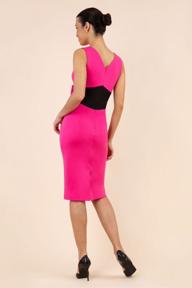 blonde model wearing Diva Catwalk Pencil sleeveless dress with rounded neckline and bow detail at the front with a contrasting black band in hibiscus pink back