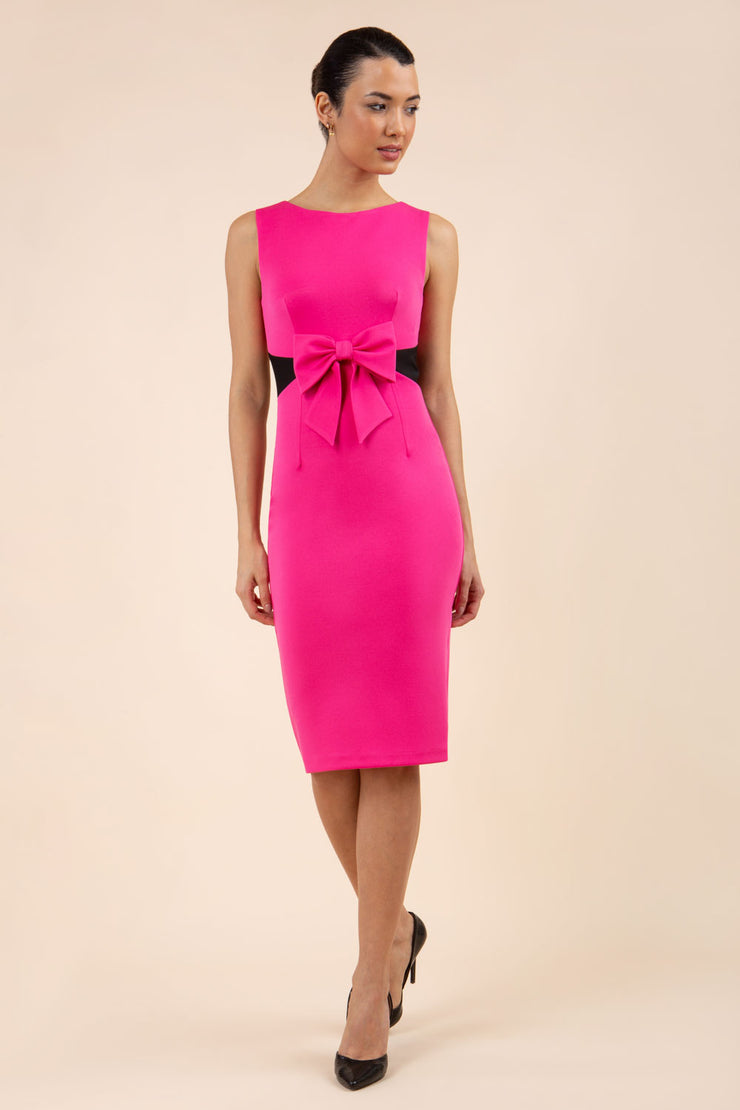 blonde model wearing Diva Catwalk Pencil sleeveless dress with rounded neckline and bow detail at the front with a contrasting black band in hibiscus pink front